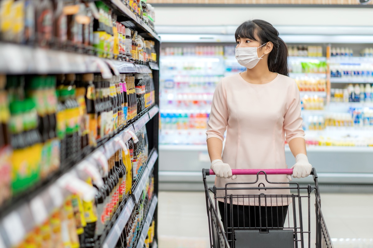 woman in grocery store shopping for sauces