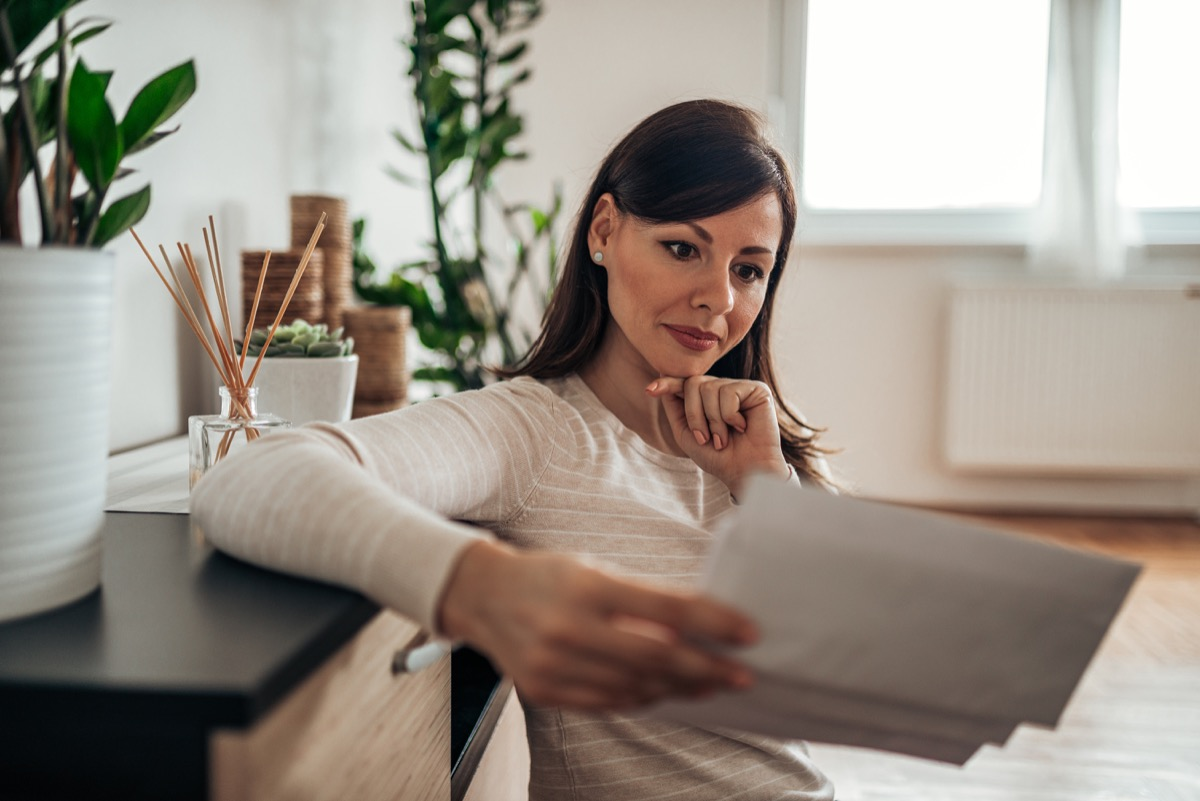 Pensive woman looking at received mail at home, holding blank envelopes.
