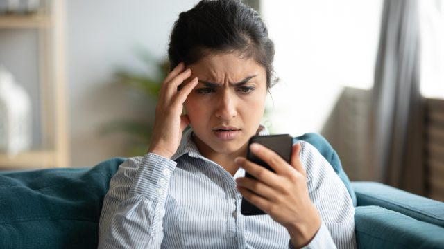 A young woman looks at her smartphone with a concerned look on her face.