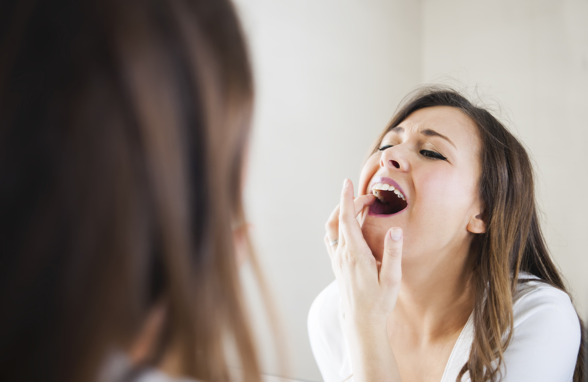 Woman looking her self in mirror, she has toothache