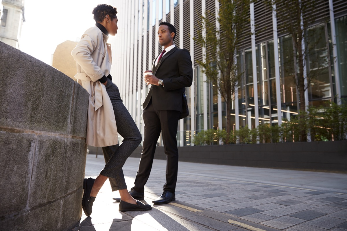 Two young adult colleagues standing on the street talking, low angle