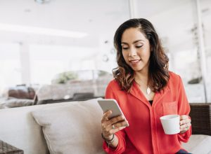 A young woman sitting on a couch checking her iPhone while holding a mug.