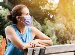 A woman sitting on a park bench while wearing a face mask.