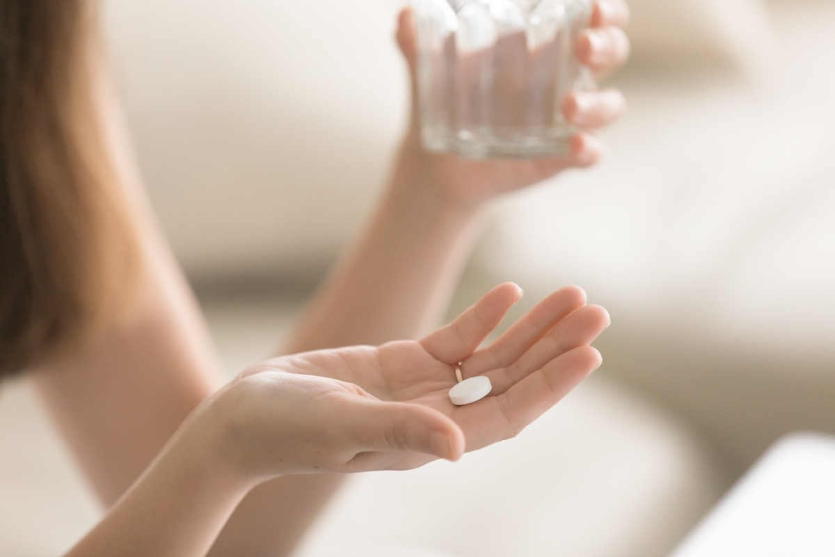woman with pill in hand holding glass of water