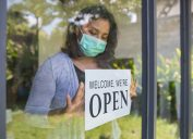 A woman wearing a face mask tapes an open sign on the front door of a business.