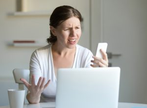 A young woman looks angrily at her cell phone while reading a text message