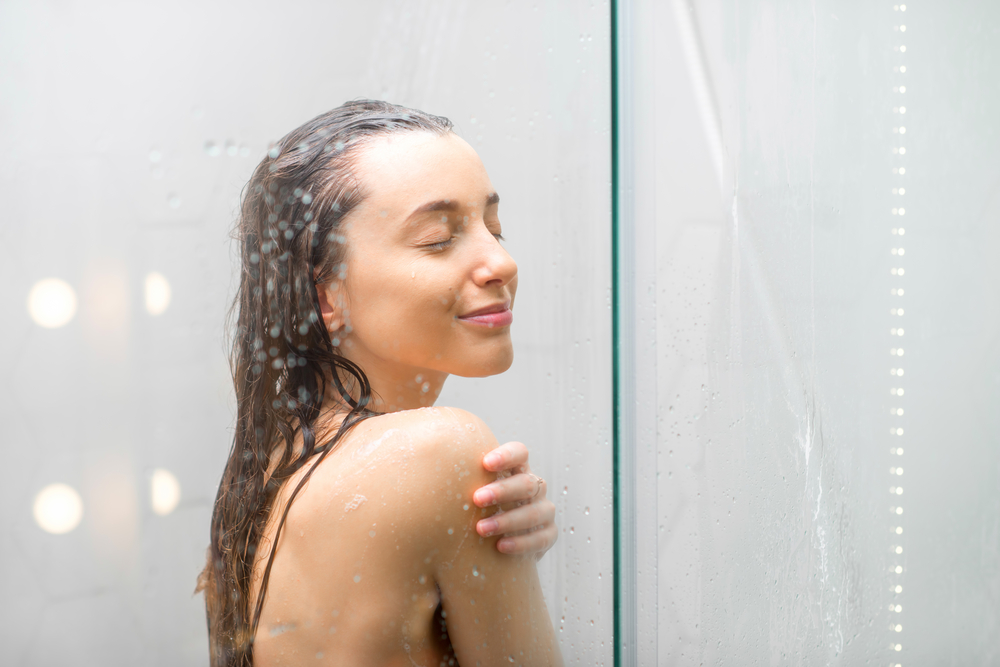 A young woman stands smiling in the shower