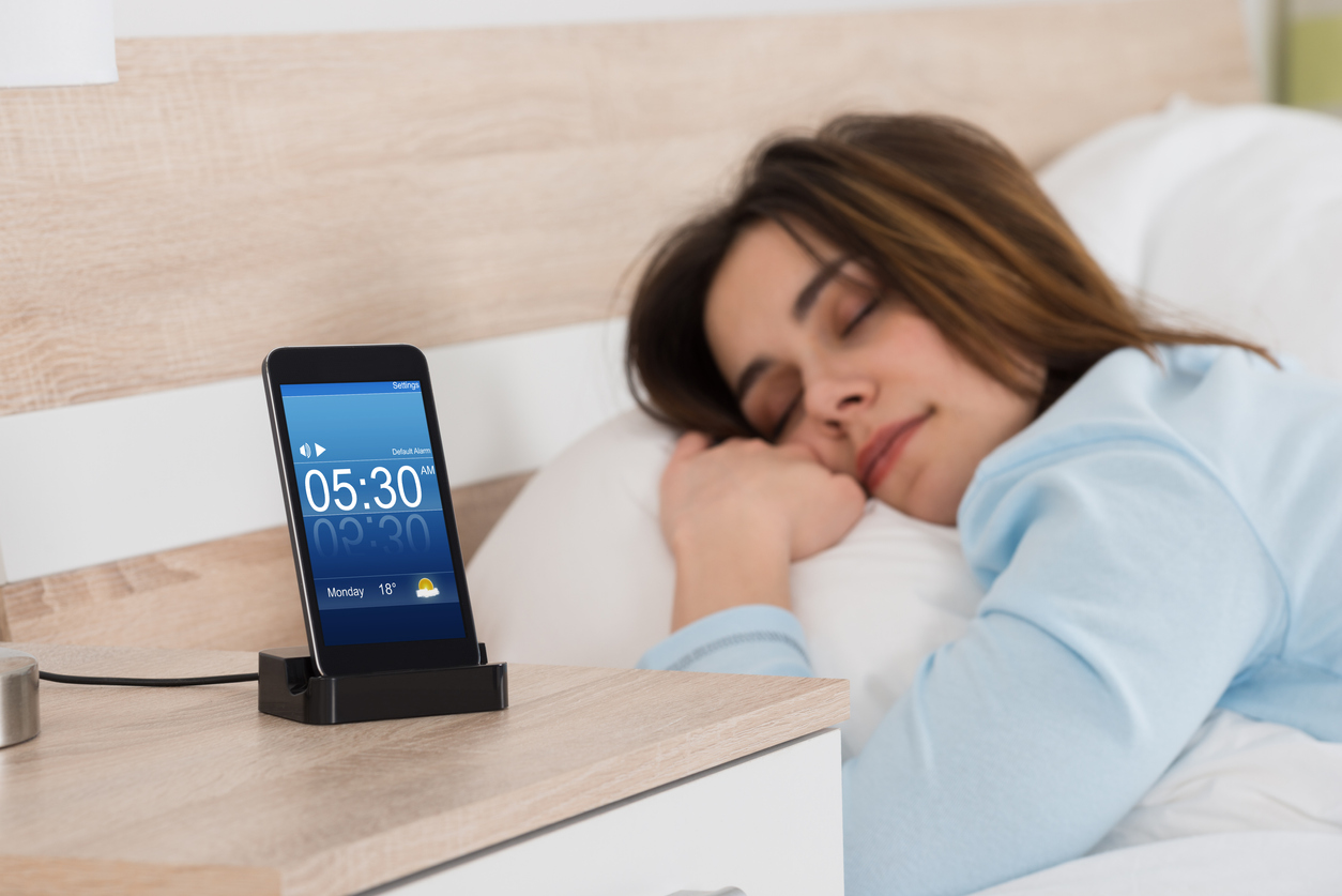A young woman sleeping next to a smartphone charging on the nightstand