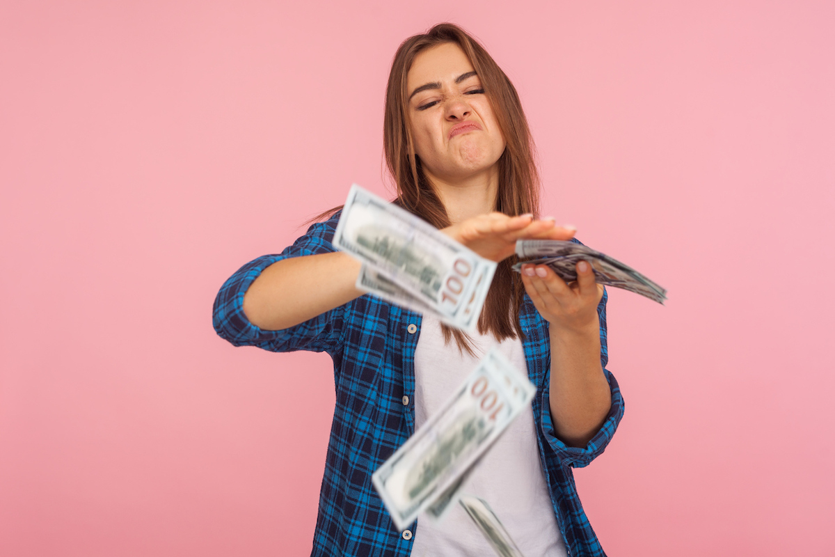 Portrait of wasteful rich girl in checkered shirt scattering dollars with arrogant grimace, boasting wealthy life, concept of careless money spending. indoor studio shot isolated on pink background