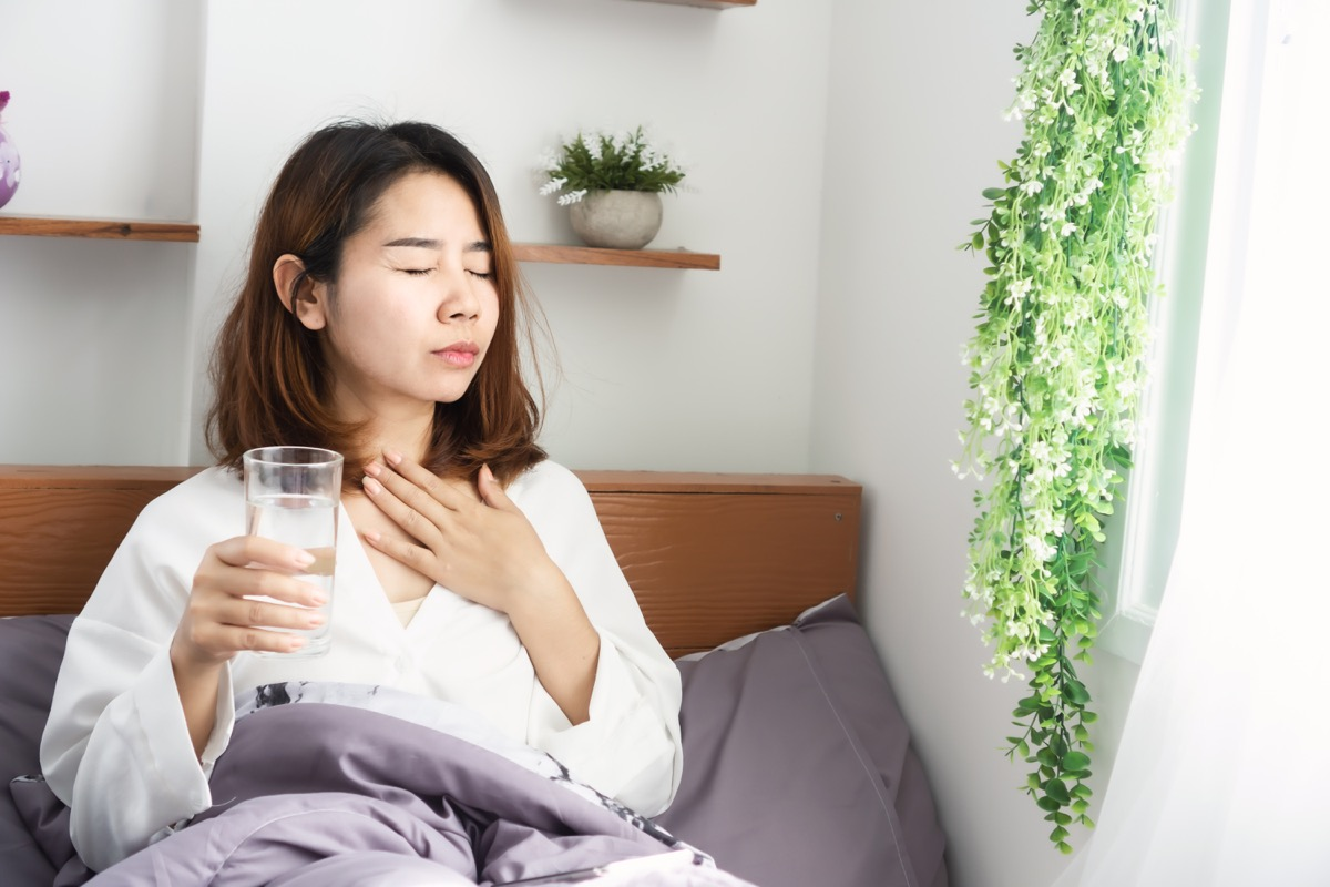 woman suffering from sore throat drinking water in her bed