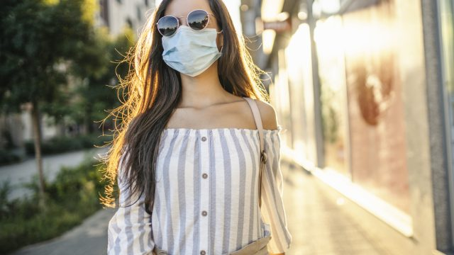 A young woman wearing a face mask and sunglasses walking down the street with the sun shining behind her.