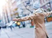 A woman wearing a winter jacket and hat takes her face mask off on a city street.