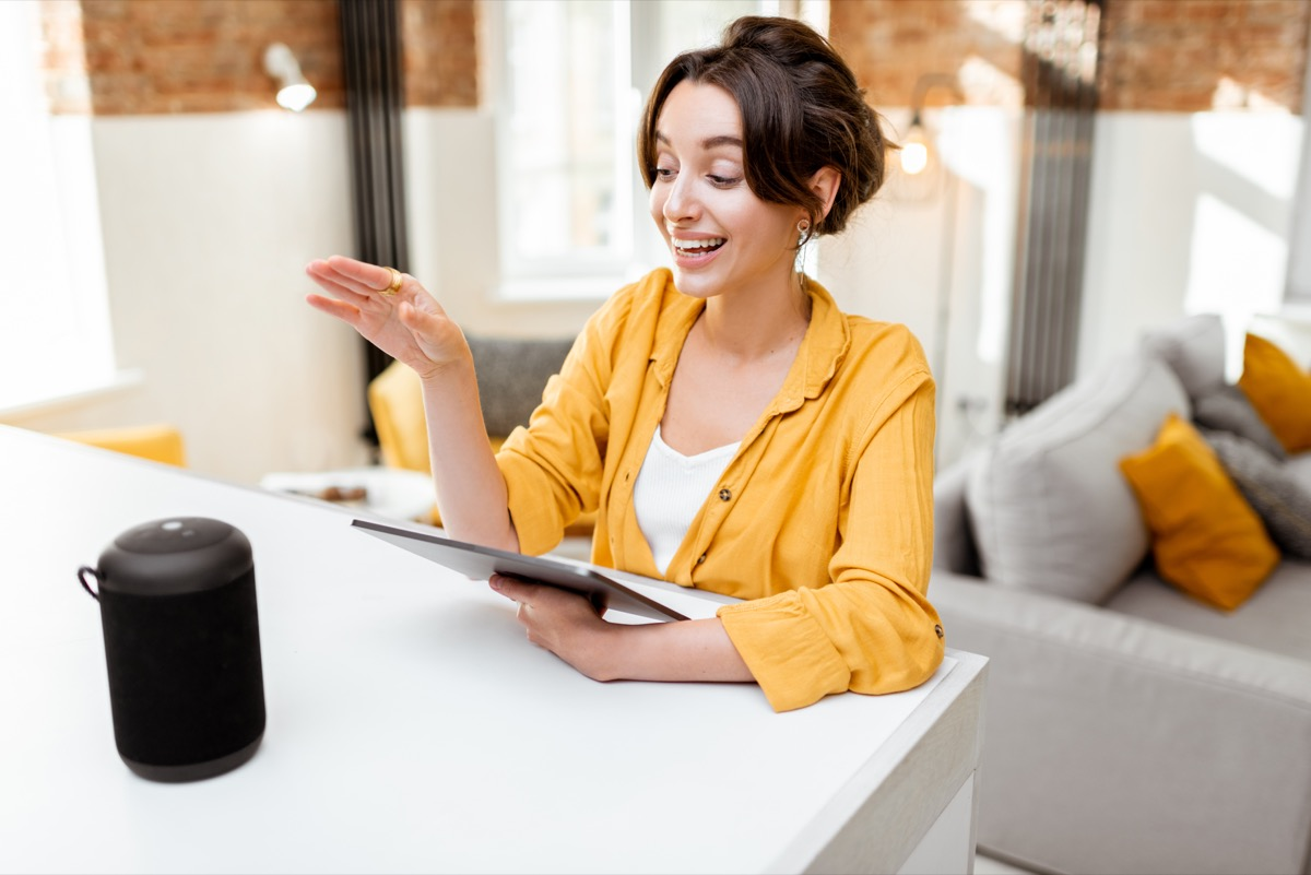 Happy young woman controlling smart home devices with a voice commands and smart speaker at home. Concept of a smart home and managing wireless devices remotely