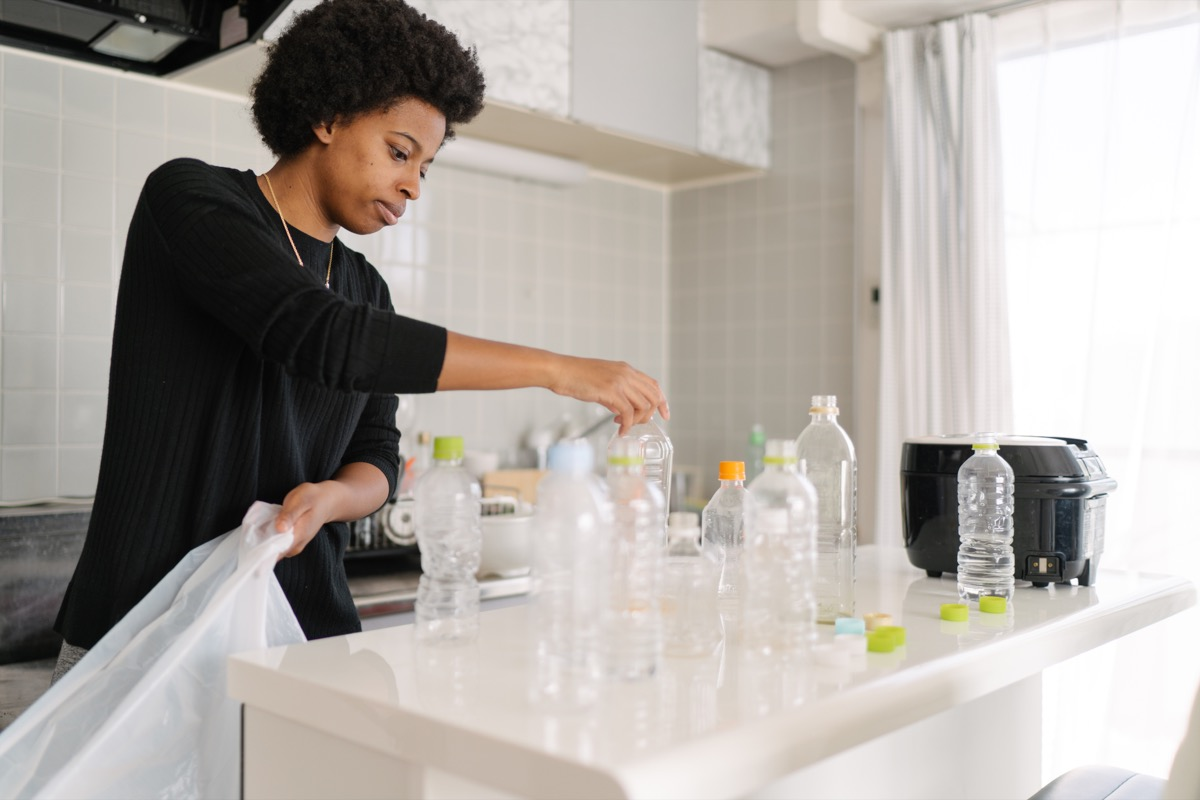 A young woman is separating wastes and pet bottles at home for recycling.
