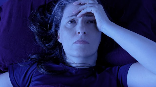 Middle aged woman lying awake in her bed at night