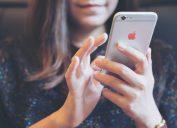 A closeup of a woman using an iPhone