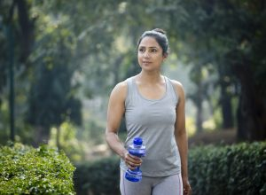 A young woman walking in the park while holding a water bottle.