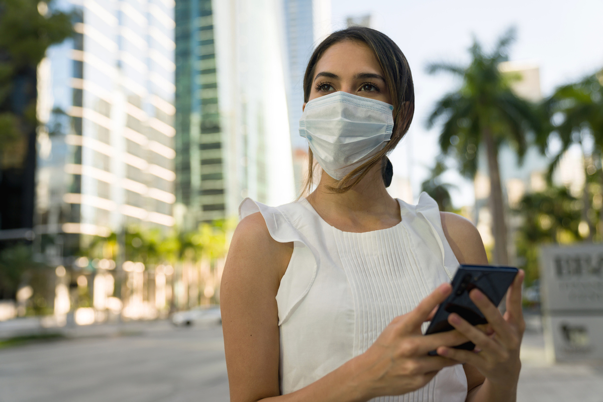 Portrait of a woman wearing a face mask on the street and checking her cell phone while outdoors during the COVID-19 pandemic