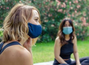 Two friends talking in the park with face masks