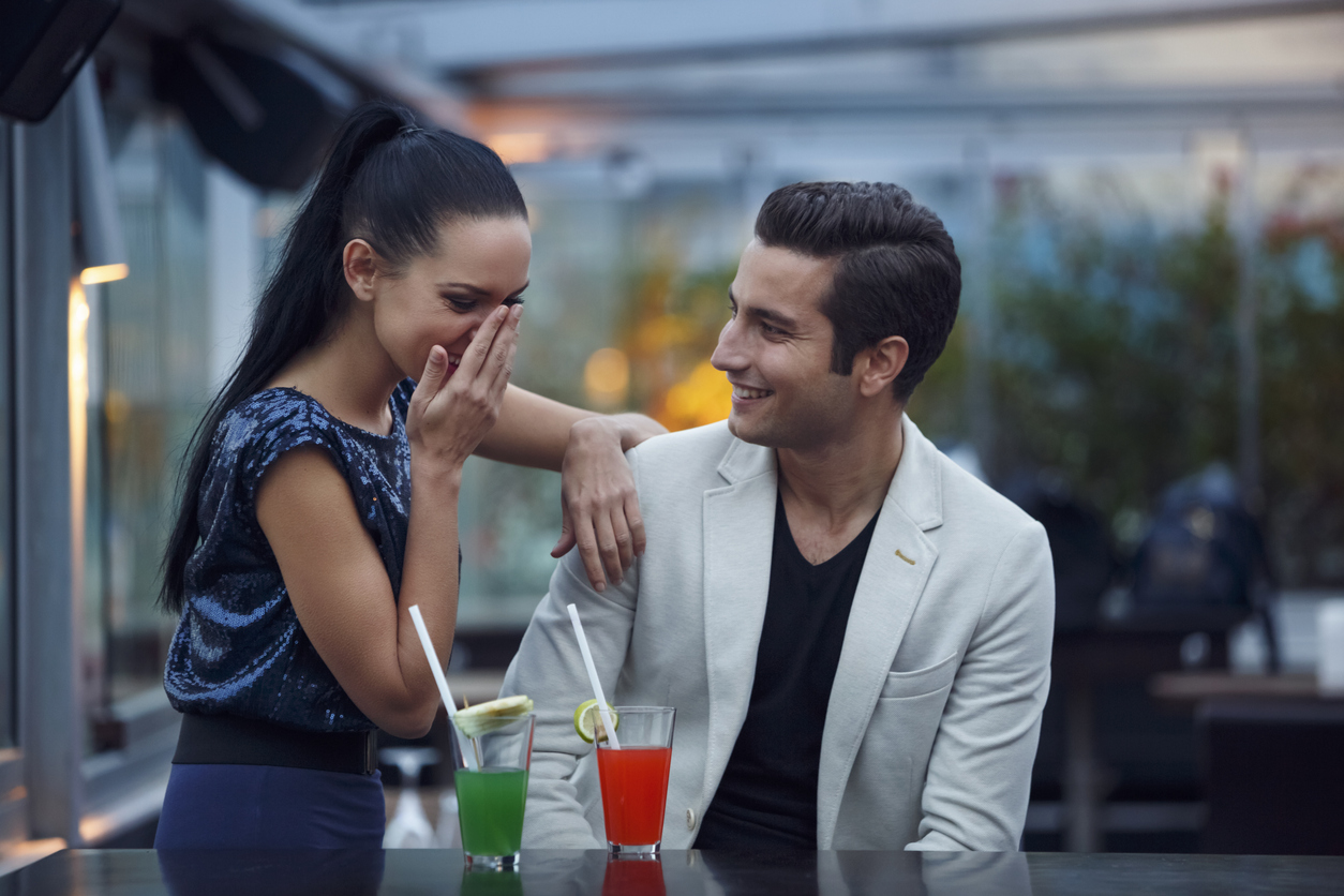 A young man and woman on a date with cocktails in front of them while the young woman covers her mouth