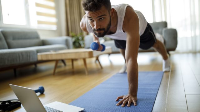 A young man exercising in his living room with his laptop, a yoga mat, and a weight.