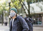 A young man wearing a face mask and a backpack stands on a city street.