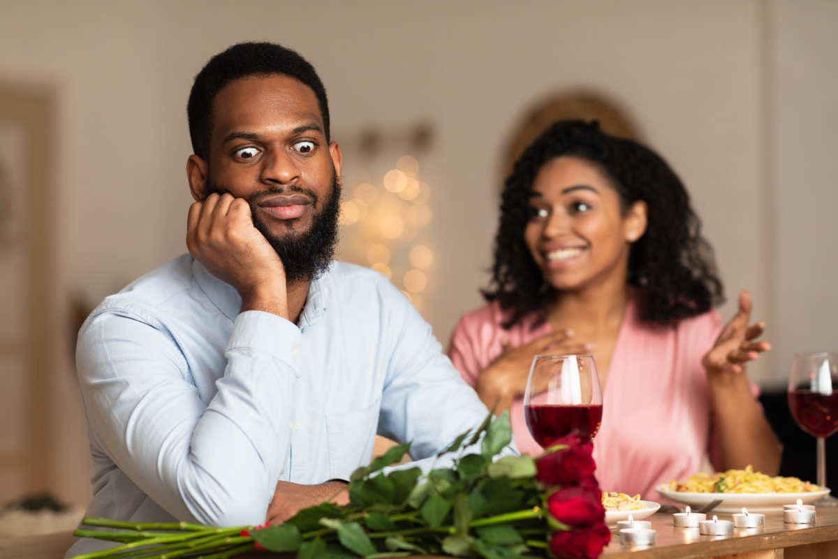 Young man being annoyed by young woman at dinner