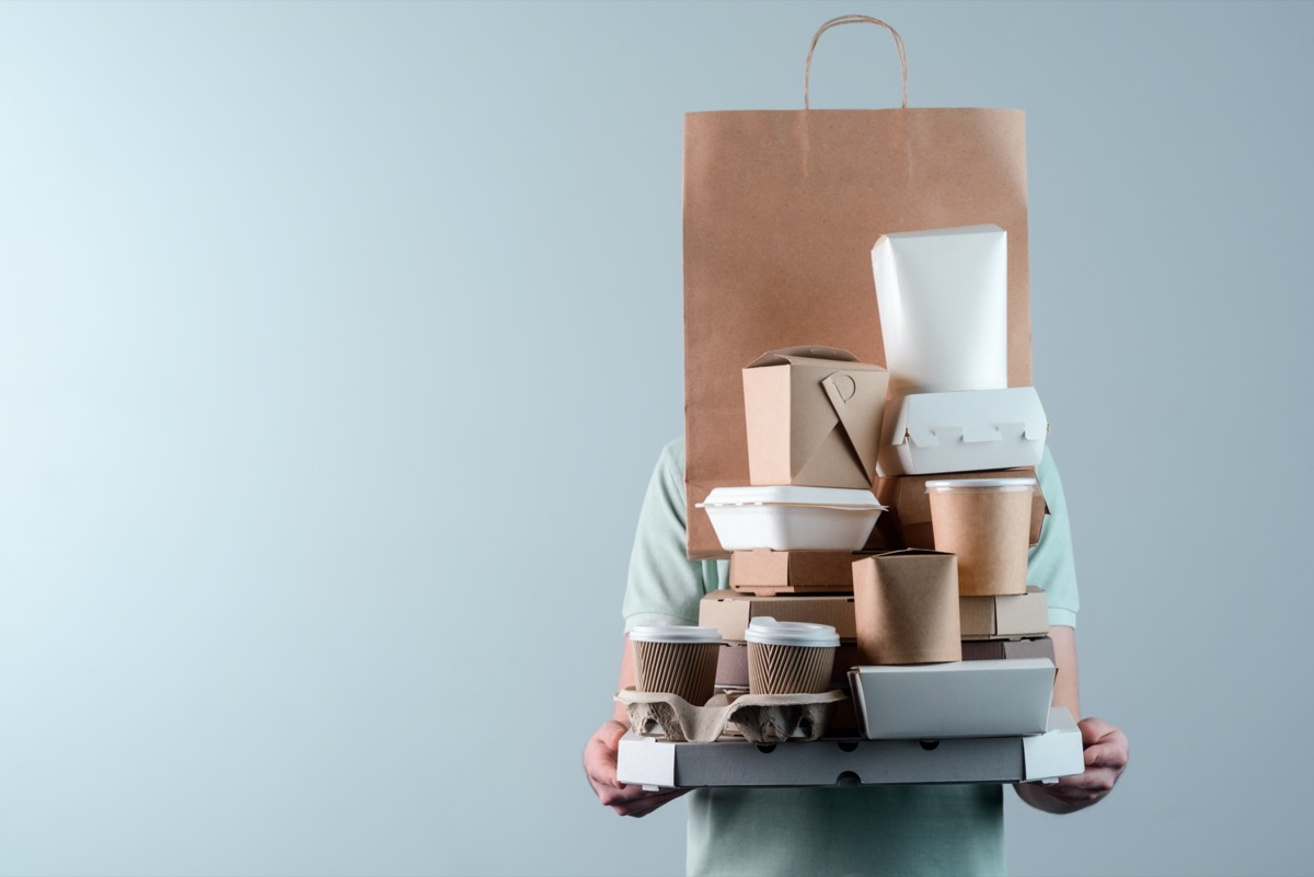 Man holding pile of delivery food