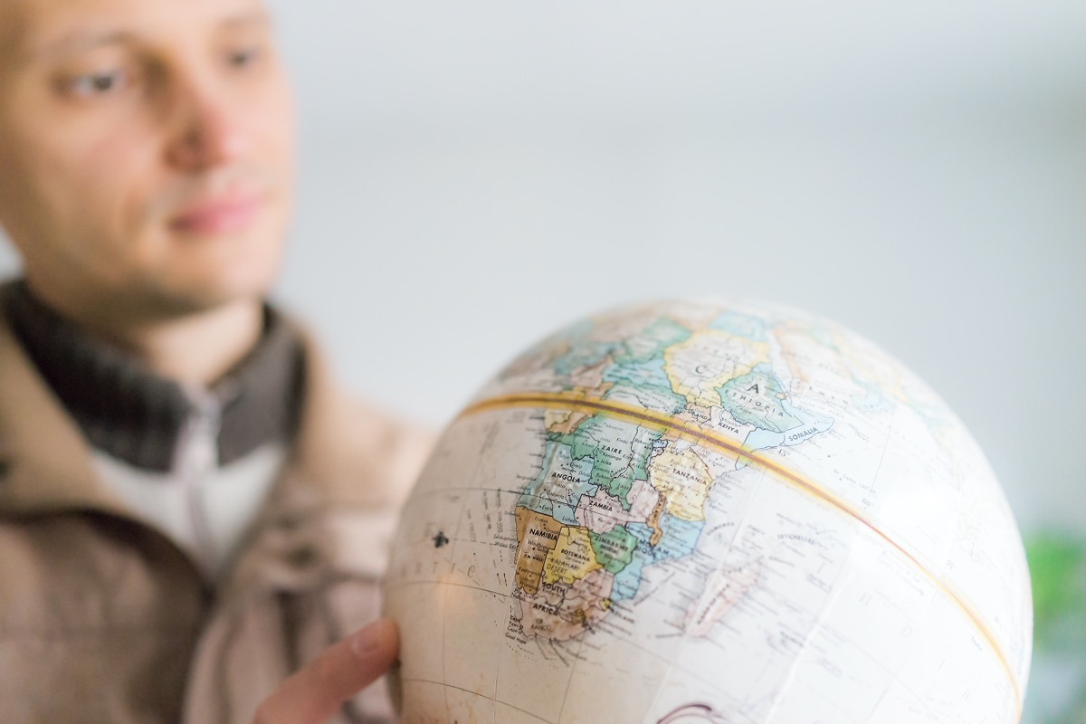 Man looking at globe with equator line