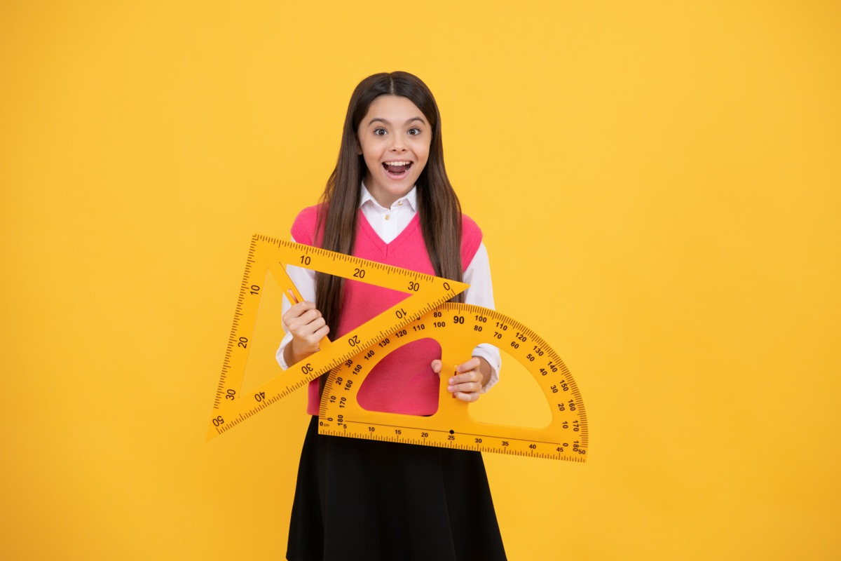 Girl holding up geometry tools