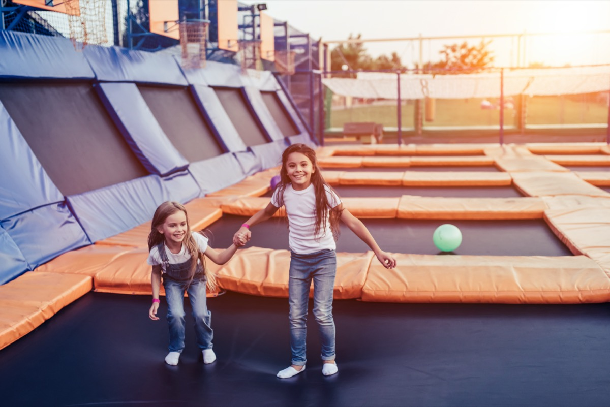 Two little girls jumping on trampoline