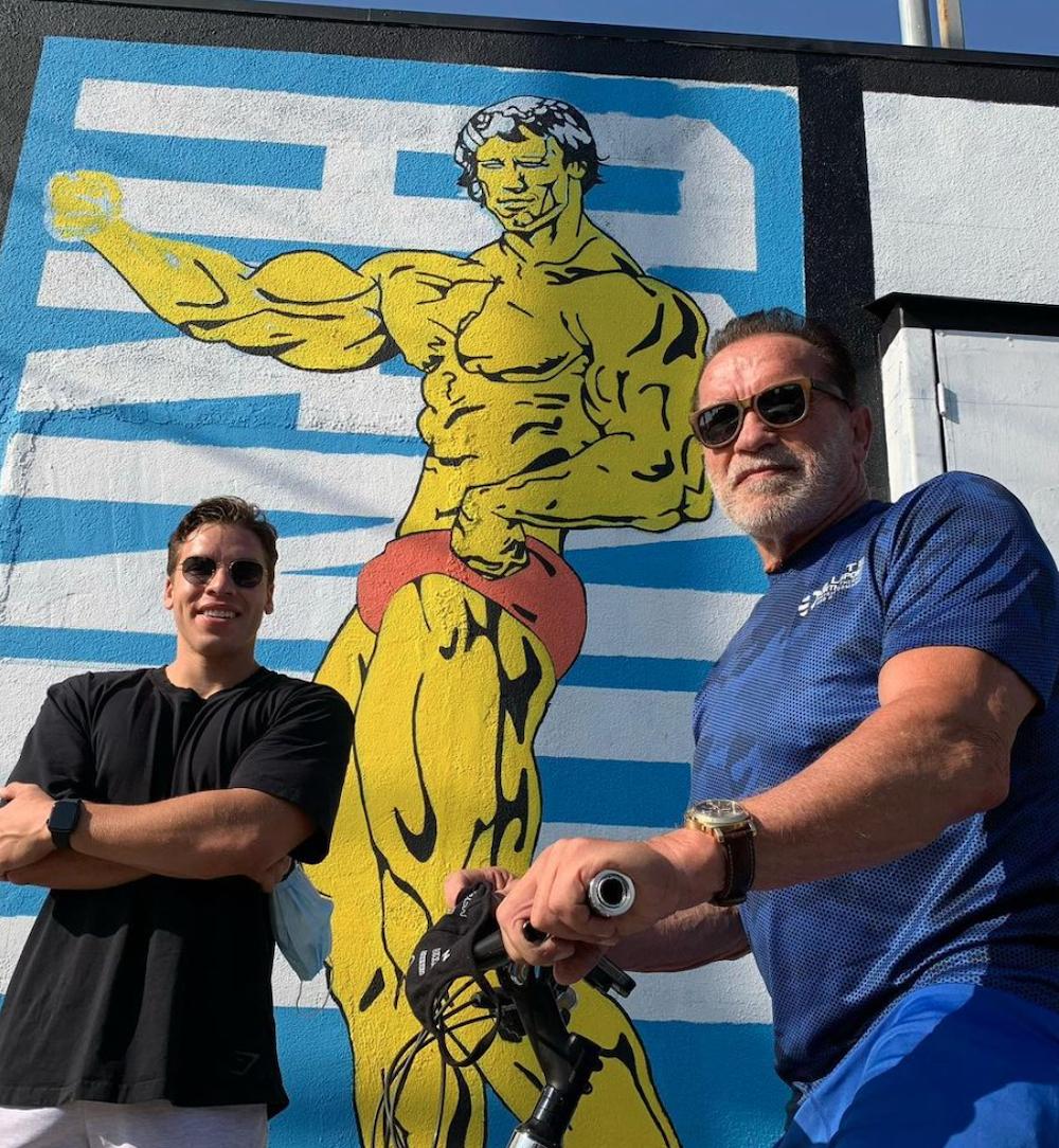 Joseph Baena and Arnold Schwarzenegger posing by a mural of Schwarzenegger