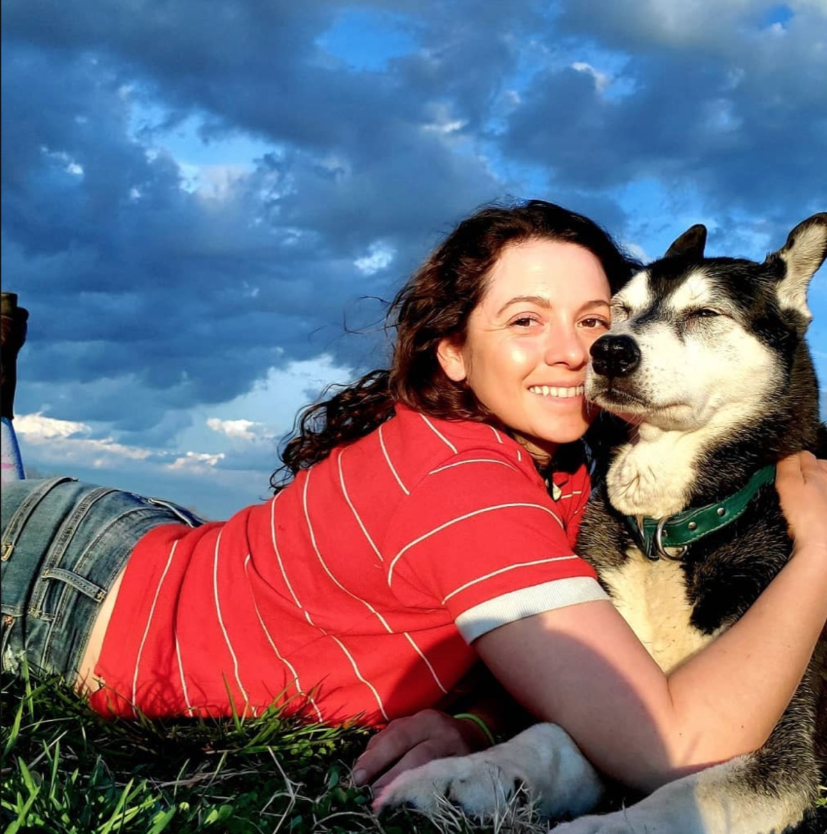 Mackenzie Rosman lying down in a red shirt hugging a black and white dog outdoors