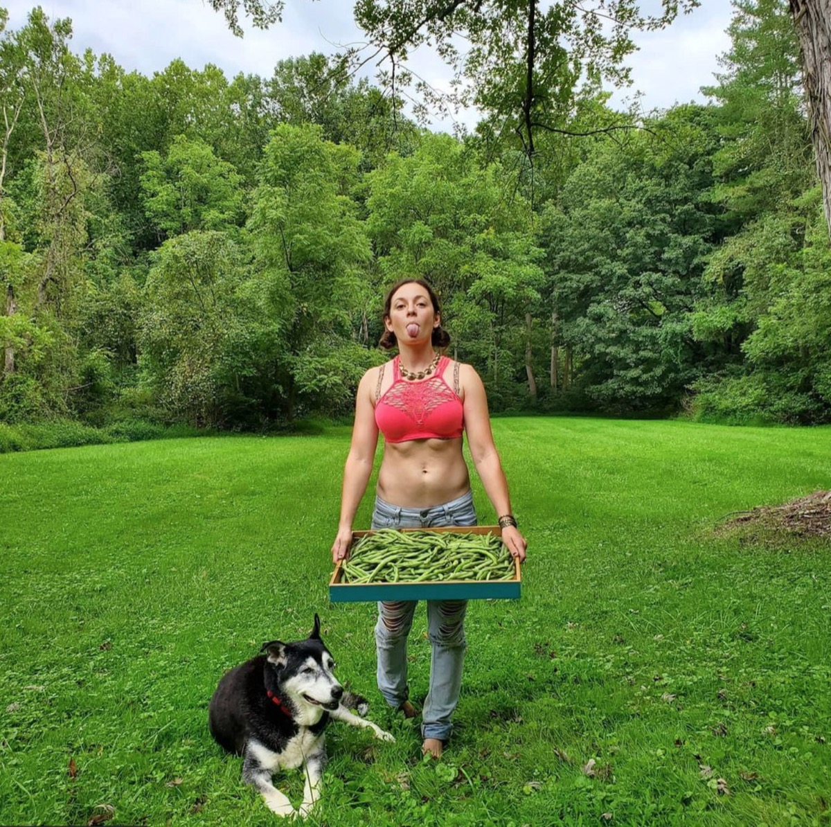 Mackenzie Rosman wearing jeans and a red crop top in a green field carrying a tray of vegetables and standing next to a black and white dog