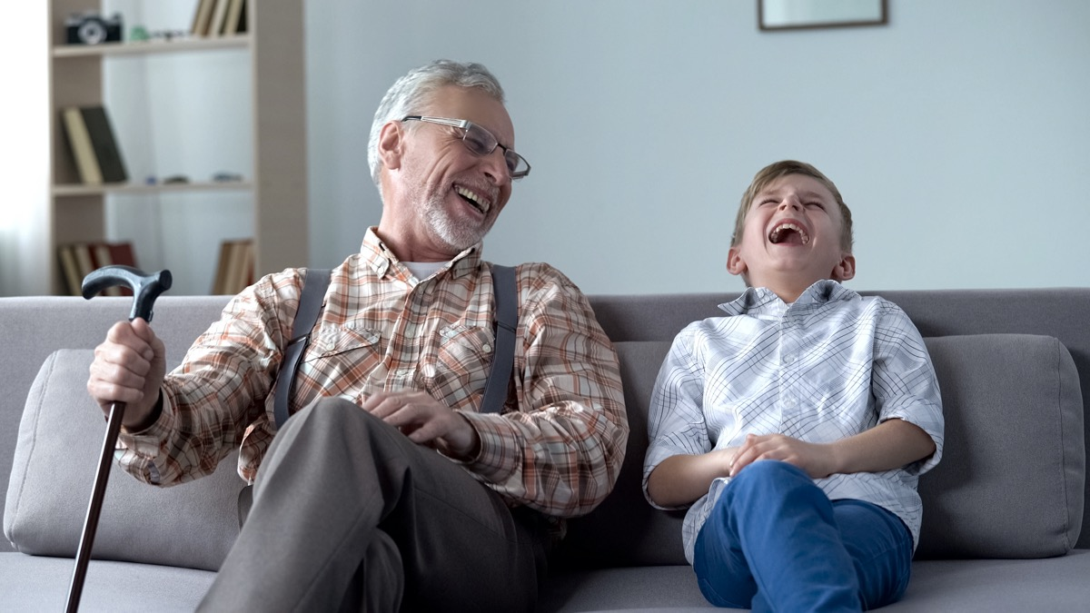 Senior man and young boy laughing on couch