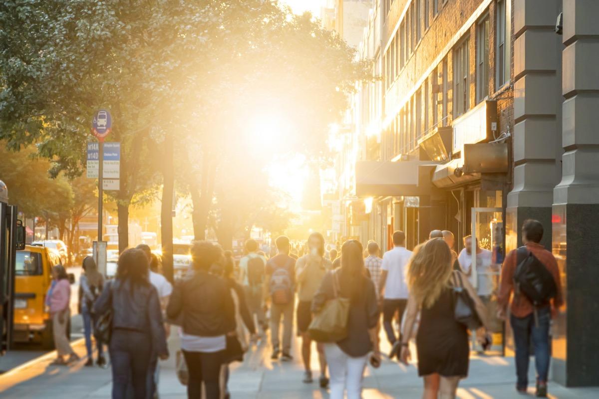 Crowded New York City sidewalk at sunset