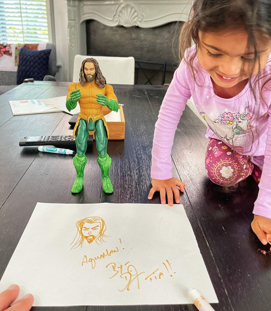 Tiana Johnson next to her dad's drawing of Aquaman