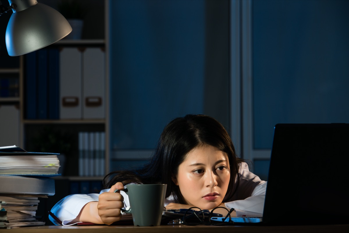 Tired woman still in office at night