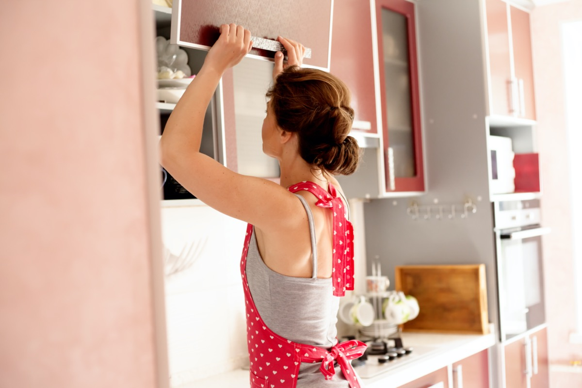 Woman looking for dishes in kitchen cabinet