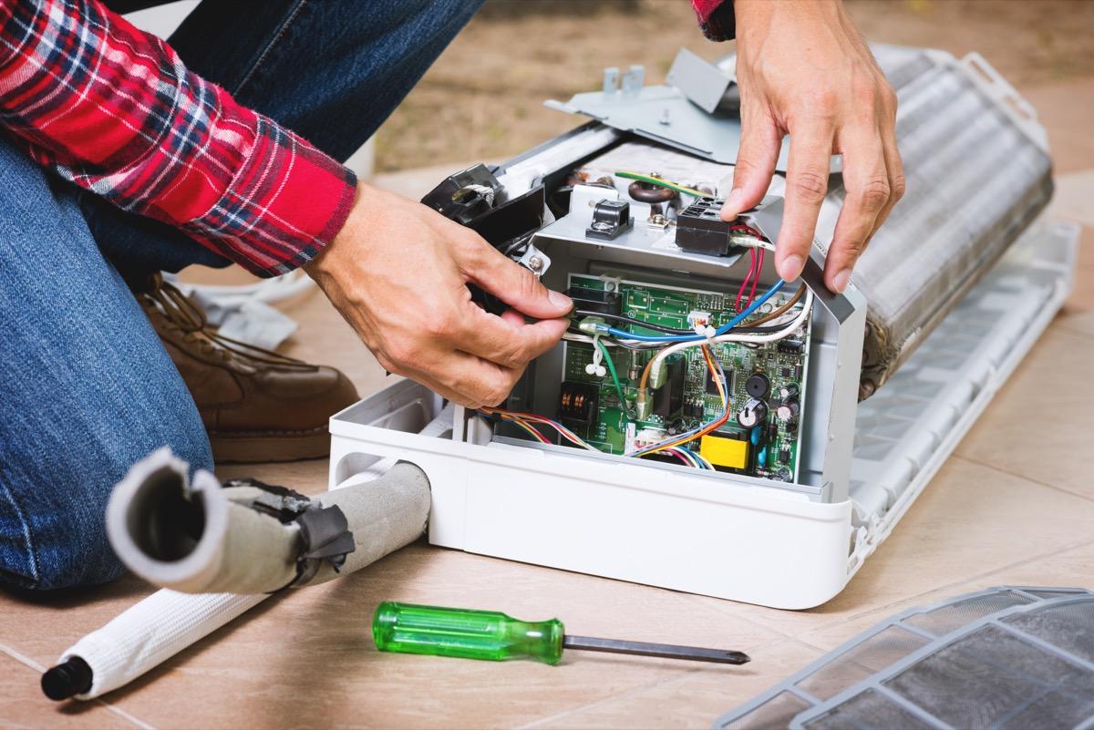 air conditioner tech repairing AC unit