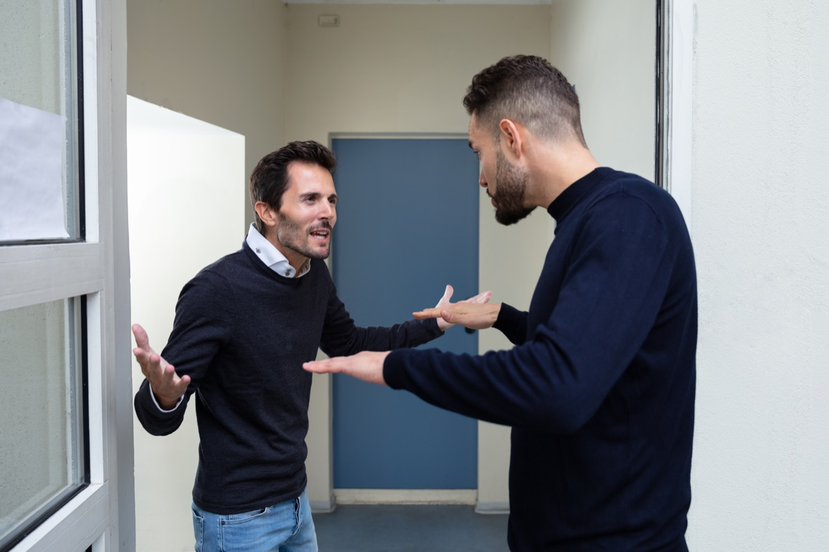 Two Young Men Standing At The Door Entrance Quarreling With Each Other