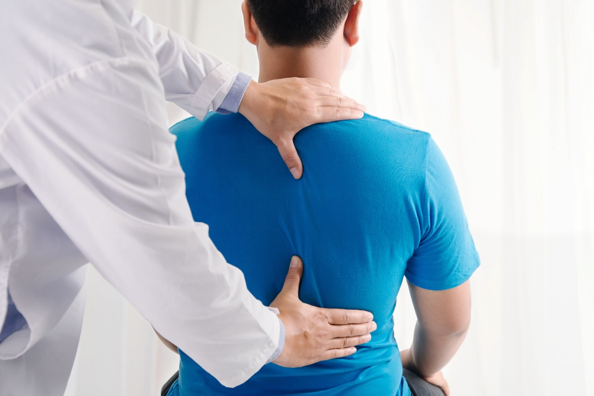 doctor touching man's back, back pain