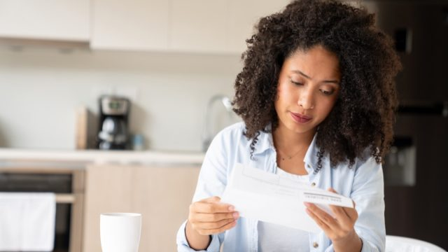 Woman looking concerned while reading her bills