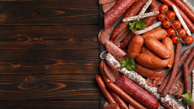 charcuterie board with sausages and other meat on wooden table