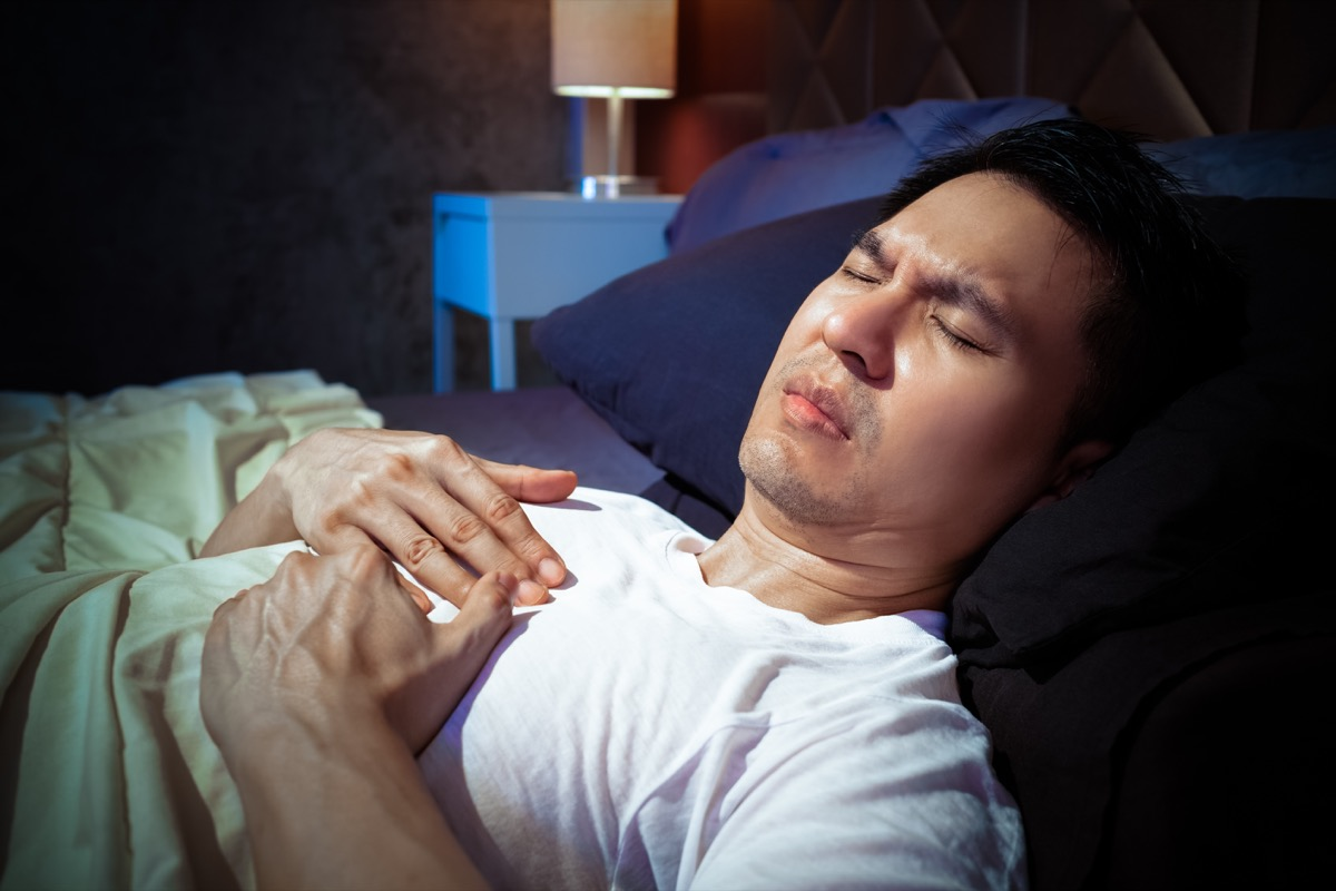 man has a heart attack symptoms while sleeping on bed at night
