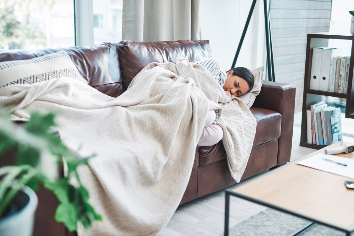 Shot of a young woman feeling sick on the sofa at home