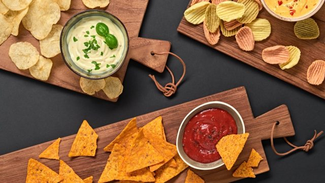 tortilla chips, potato chips, and veggie chips on wooden boards on a black table