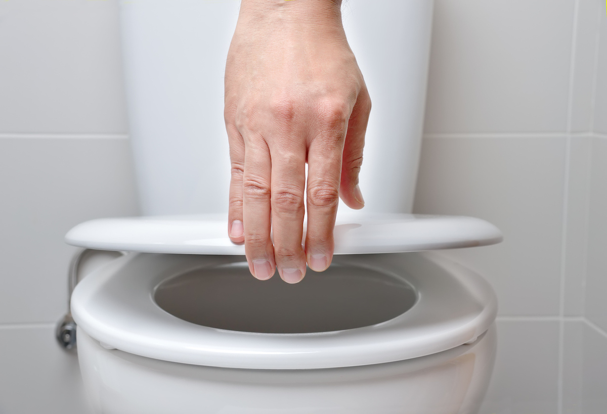 hand of a man closing the lid of a toilet