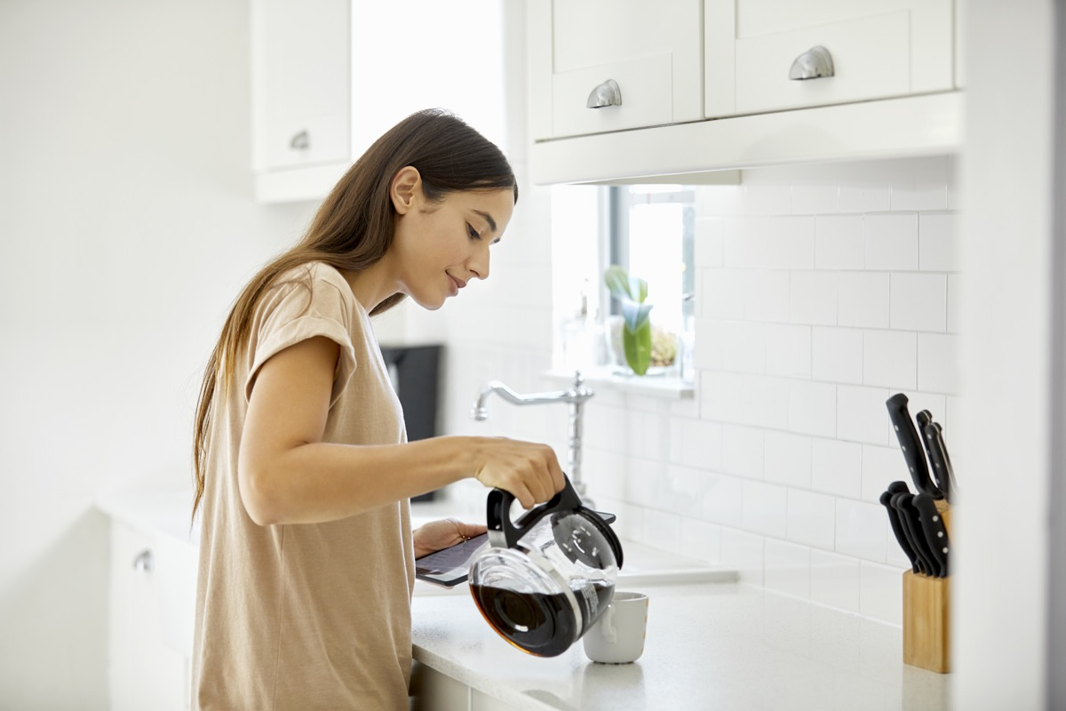Side view of young woman pouring coffee in cup. Beautiful female is standing at kitchen counter. She is in casual at home.
