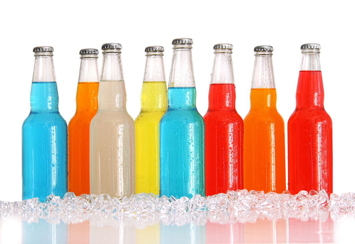Bottles of multi-color wine cooler drinks with ice on white background
